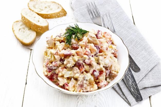 鶏肉、ピーマン、トマト、卵、チーズをマヨネーズとニンニクで味付けしたサラダ、灰色のナプキン、パン、木の板の背景にフォーク