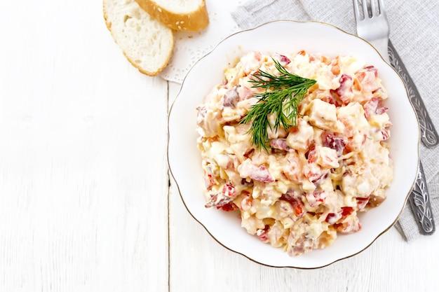 鶏肉、ピーマン、トマト、卵、チーズをマヨネーズとニンニクで味付けしたサラダ、上から軽い木の板に皿、タオル、パン、フォークを入れて