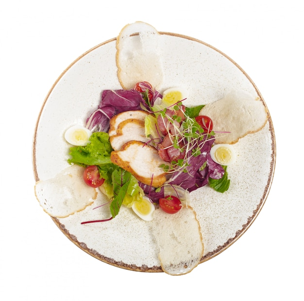 Salad with chicken on a white plate