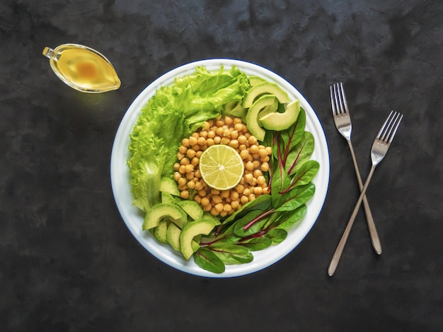 Salad with chickpeas and avocado on a plate. top view.
