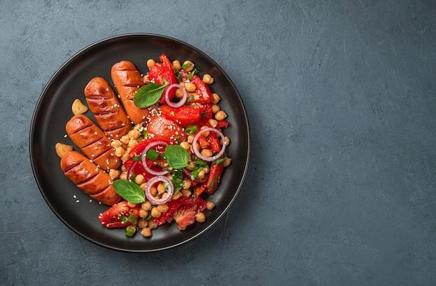 ひよこ豆のトマトとゴマとソーセージの暗い背景のサラダ