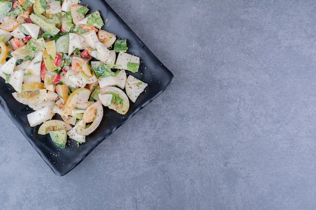 Salad with chopped herbs and vegetables on concrete surface