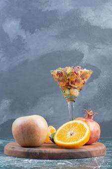 Insalata con frutta di stagione tritata su superficie blu.