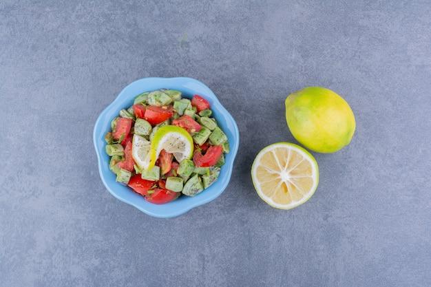 Салат с измельченными помидорами и стручковой фасолью подается с лимоном