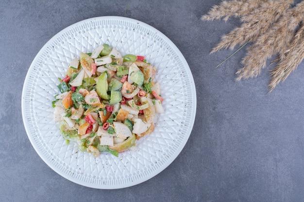青い表面に刻んだ野菜とハーブのサラダ