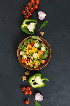 Salad with colorful vegetables on black kitchen counter