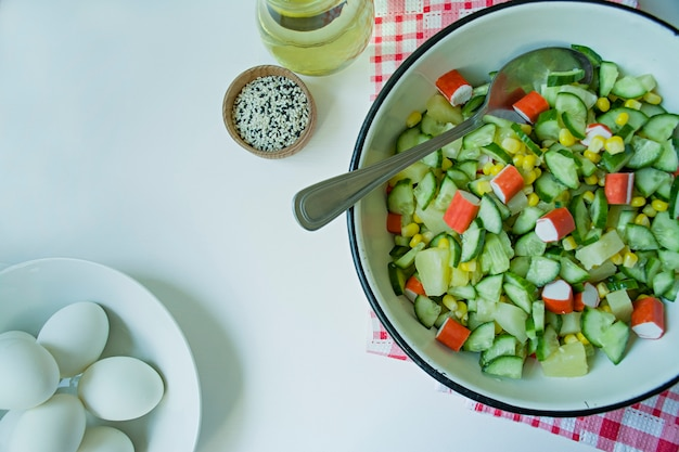 Salad with corn, crab sticks, cucumbers in a white bowl on a white background.