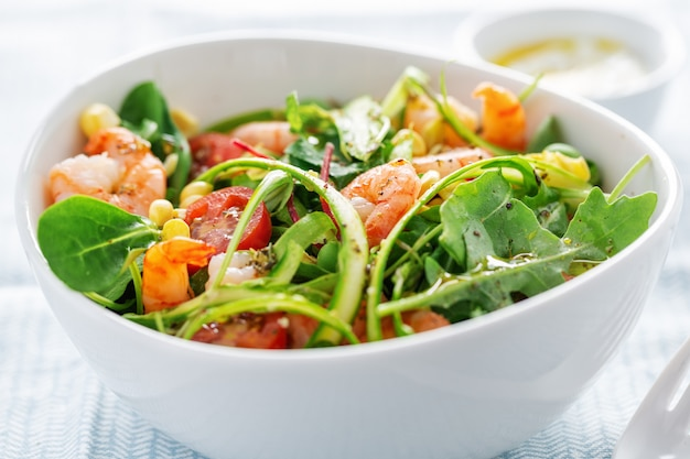 Salad with corn, shrimps and asparagus served in bowl.
