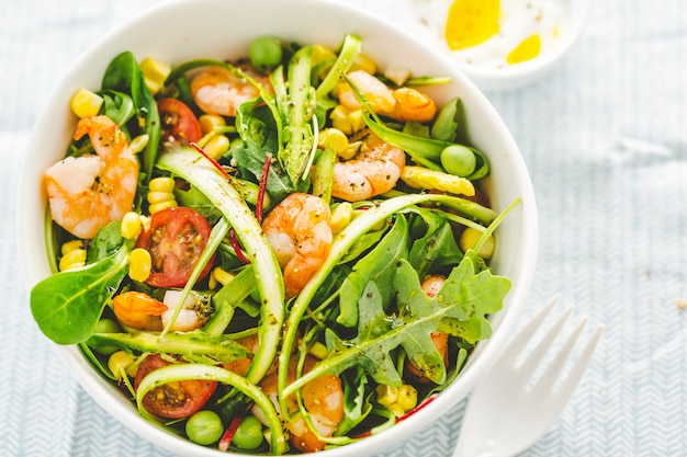 Salad with corn, shrimps and asparagus served on plate.