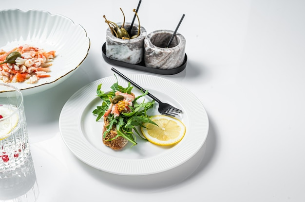 식탁에 게살을 곁들인 샐러드. 흰색 배경. 평면도. 공간을 복사합니다.