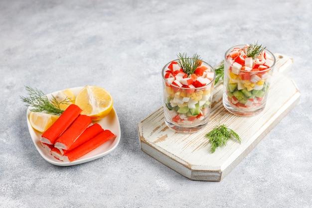 Салат с крабовыми палочками, яйцом, кукурузой и огурцом.