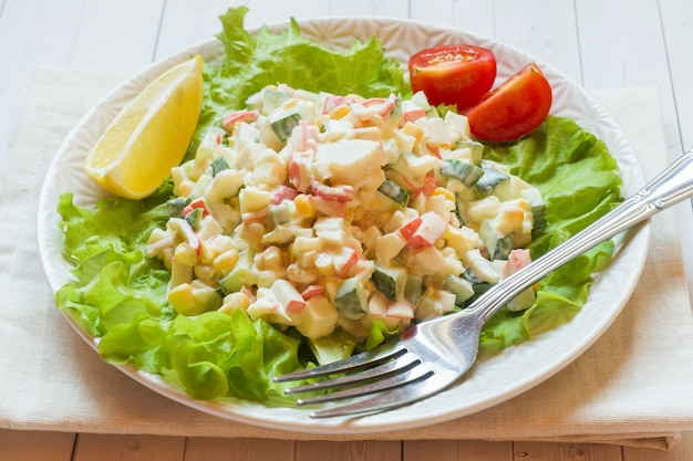 Salad with crab sticks, sweet corn, cucumber, eggs and mayonnaise