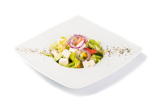 흰색 배경에 오이, 토마토, 치즈, 양파, 허브를 넣은 샐러드. 격리
