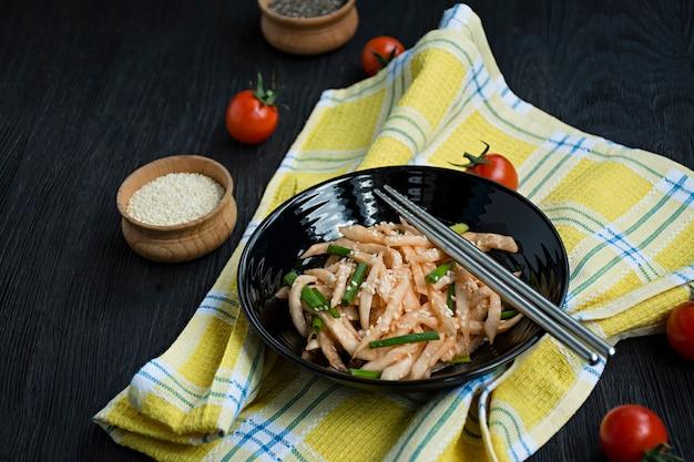 Salad with daikon radish, green onions, honey and red chili powder. asian salad. flat lay. . dark .