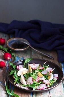 Салат с одуванчиком, яйцом и редисом на деревянном фоне. деревенский стиль