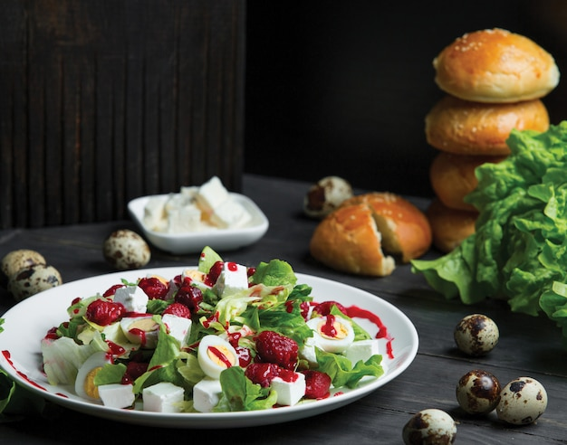 Salad with dry tomatoes and mozarella cubes with bread buns