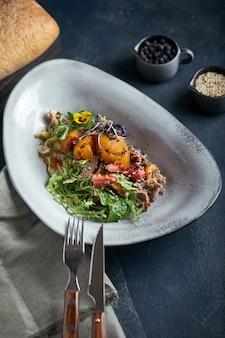 Салат с утиной клубникой и манго на темном, сдержанном тоне.
