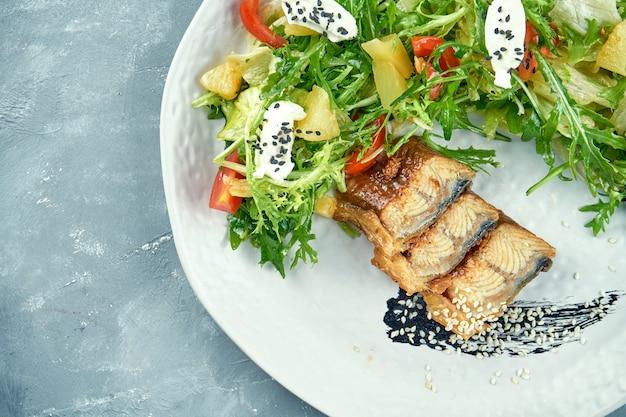 Салат с угрем, рукколой, листьями и сливочным сыром в белой тарелке. салат из морепродуктов. вид сверху