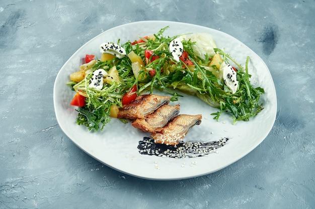 Салат с угрем, рукколой, листьями и сливочным сыром в белой тарелке. салат из морепродуктов