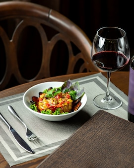 Salad with eggplant and glass of red wine