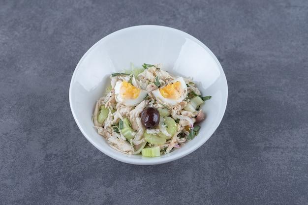 白いボウルに卵とさいの目に切った鶏肉のサラダ。