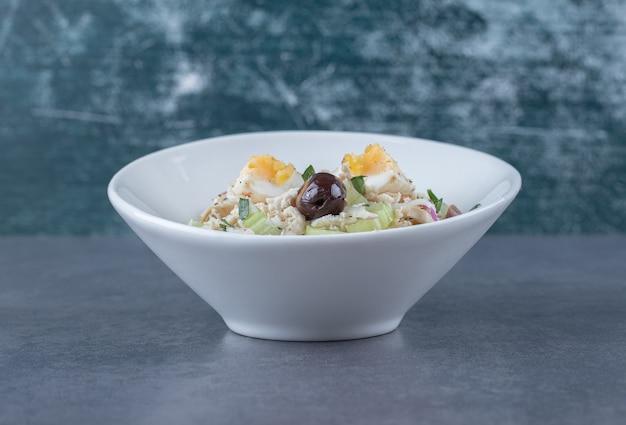 Салат с яйцами и нарезанной кубиками курицей в белой миске.