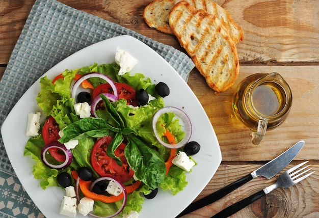 Salad with feta cheese, olives, tomatoes and lettuce and basil on wooden surface