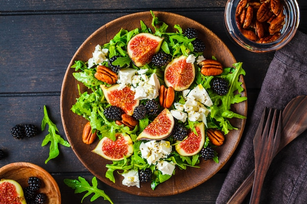 Salad with figs, feta cheese and blackberries in a wooden plate on dark background, top view,