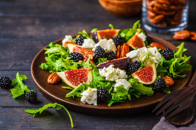 Salad with figs, feta cheese and blackberries in a wooden plate on dark