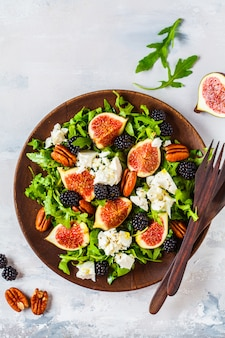 Salad with figs, feta cheese and blackberries in a wooden plate on white background, top view,