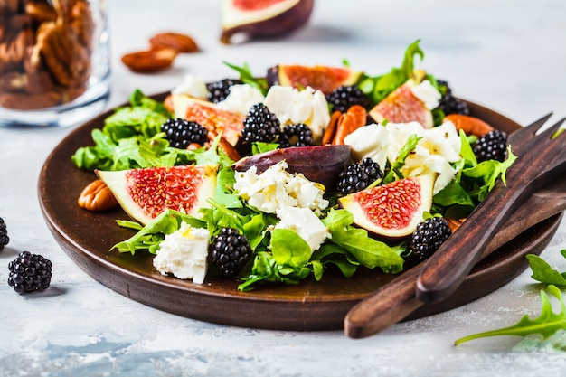 Salad with figs, feta cheese and blackberries in a wooden plate on white