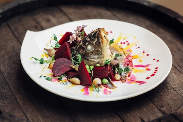 Salad with fish head on wooden barrel