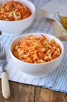 Salad with fresh cabbage, carrots and olive oil in a white bowl on a wooden table