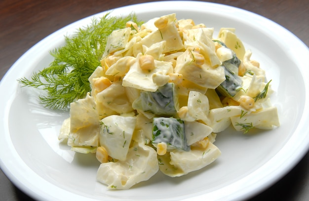 Salad with fresh cucumbers, eggs, corn and mayonnaise
