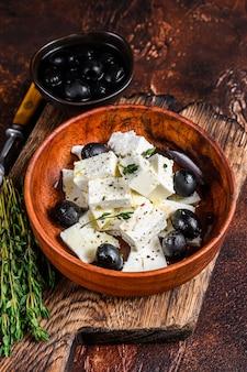 신선한 페타 치즈, 타임, 올리브가 들어간 샐러드. 어두운 배경.