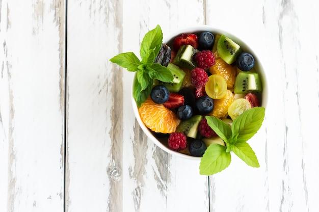 Салат со свежими фруктами и ягодами, листьями мяты на белом деревянном фоне. вид сверху.