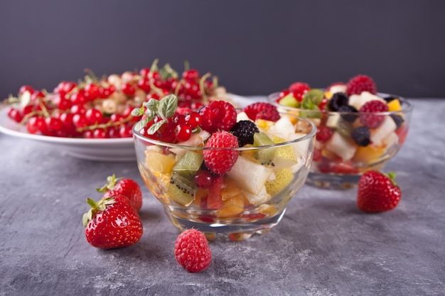 Salad with fresh fruits and berries on a bowls on the concreate background
