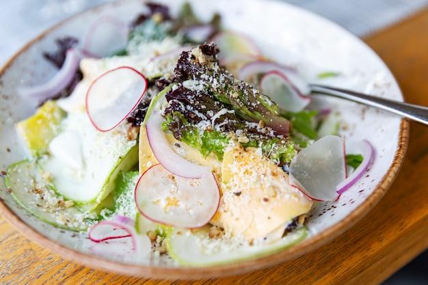 Салат со свежей зеленью, редисом и сыром на тарелке.