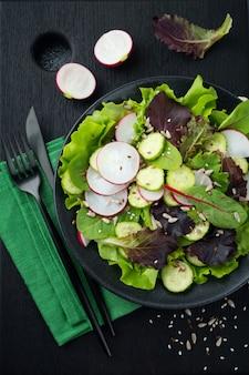 Салат из свежего редиса, рукколы, свеклы, мангольда, семечек, льна и кунжута на черном фоне