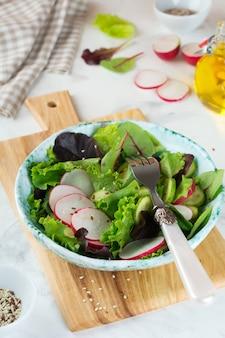 Салат из свежего редиса, рукколы, свеклы, мангольда, семечек, льна и кунжута на светлом фоне
