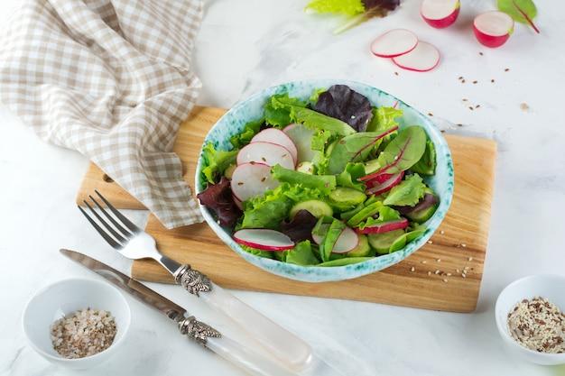 Салат из свежего редиса, рукколы, свеклы, мангольда, семечек, льна и кунжута на светлой поверхности.