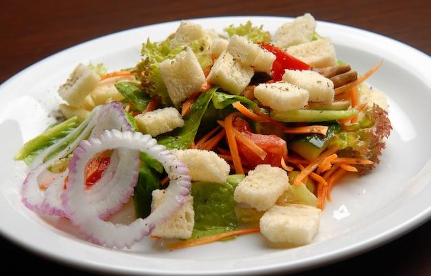 Салат из свежих овощей и сыра, панировочных сухарей и лука на тарелке