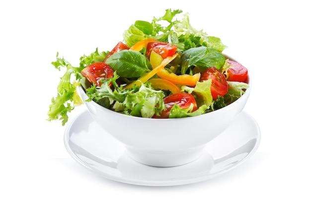 Салат со свежими овощами и зеленью на белом фоне