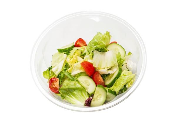 白い表面に新鮮な野菜を分離したサラダ。上面図。