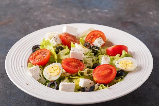 新鮮な野菜のサラダ:トマト、ウズラの卵、レタス、チーズ、ブラックオリーブ。ダイエットと健康食品のコンセプト。