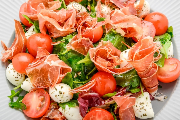 Salad with fresh vegetables with dried tomatoes, meat and mustard, mozzarella, prosciutto