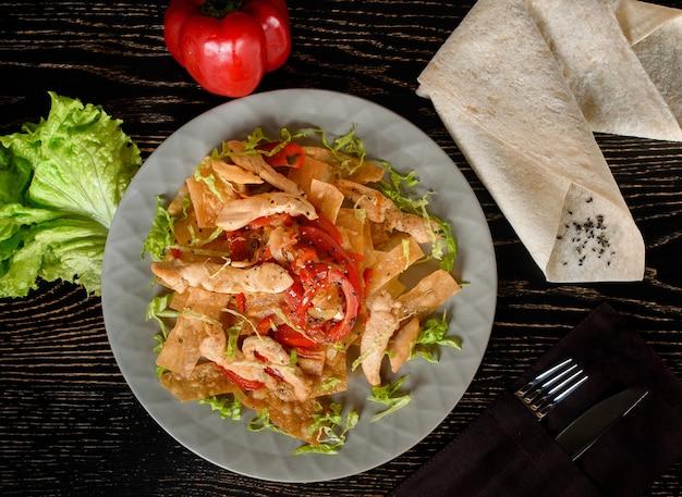 어두운 나무 테이블에 회색 접시에 프라이드 치킨, lavash, 고추, 양파, 양상추와 샐러드. 그루지야 요리. 아름다운 테이블 세팅.
