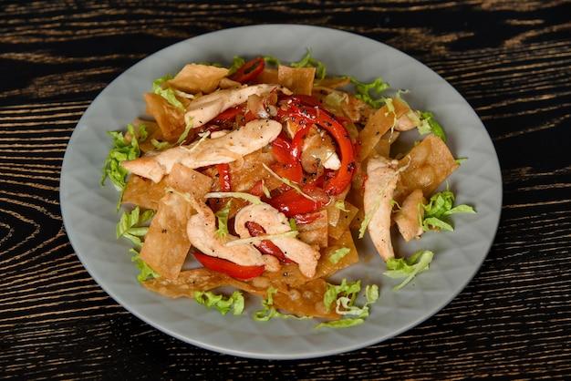 어두운 나무 테이블에 회색 접시에 프라이드 치킨, lavash, 고추, 양파, 양상추와 샐러드. 그루지야 요리.