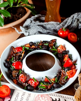 Salad with fried eggplants, tomatoes, olives, chopped scallion and sesame seeds