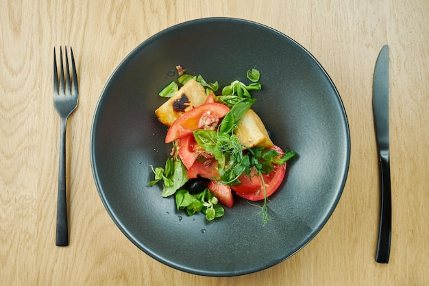 Salad with fried halumi cheese cherry tomatoes and microgreen in black bowl on wooden table. restaurant food